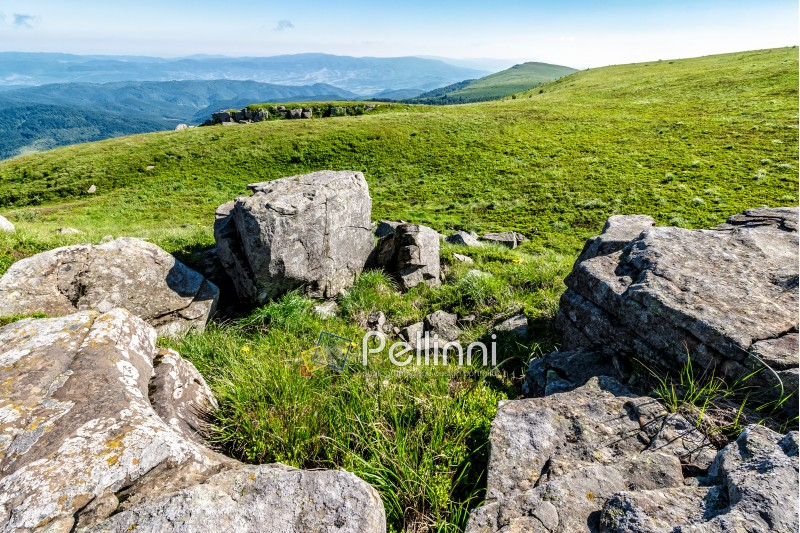mountain landscape with stones laying among the grass on top of the hill side under the cloudy summer sky