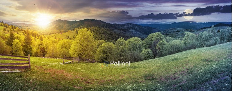 day and night time change above panorama of mountainous countryside in springtime. beautiful highland landscape with sun and moon. wooden fence on the grassy field. row of trees along the hill