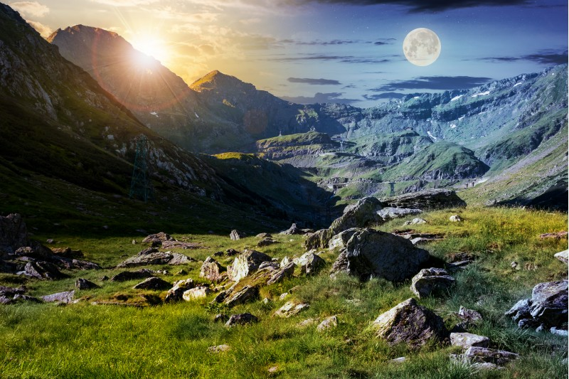 time change concept in Transfagarasan valley. rocks on grassy meadow and slopes lit by sun and moon simultaneously. half of the valley in shade of mountain ridge