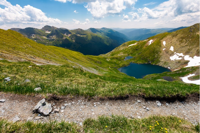tourist foot path in Fagarasan mountains, Romania. gorgeous view from the hillside in to the distant valley. lake Capra down the grassy slope. amazing summer scenery under the blue sky with few clouds
