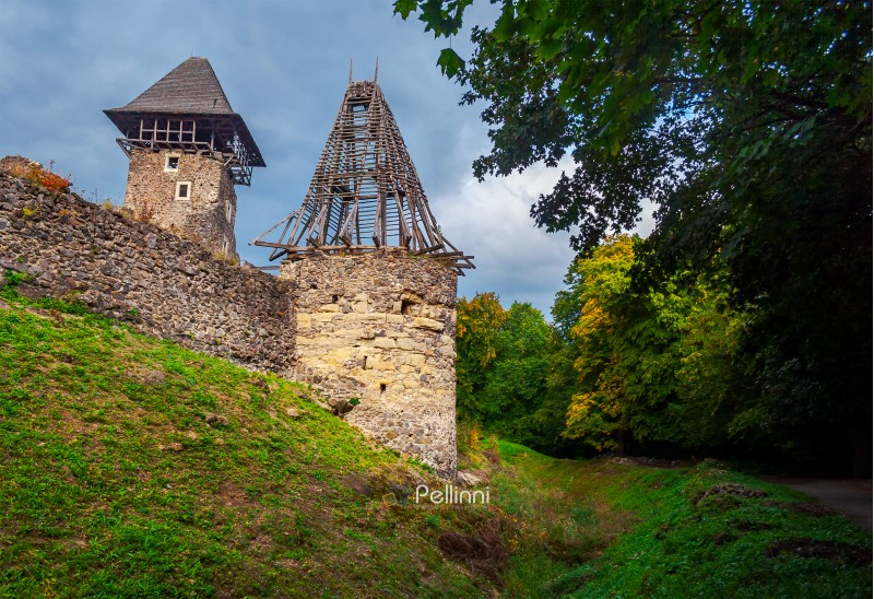 two towers of Nevitsky castle. cloudy autumn weather. some yellow foliage on the trees