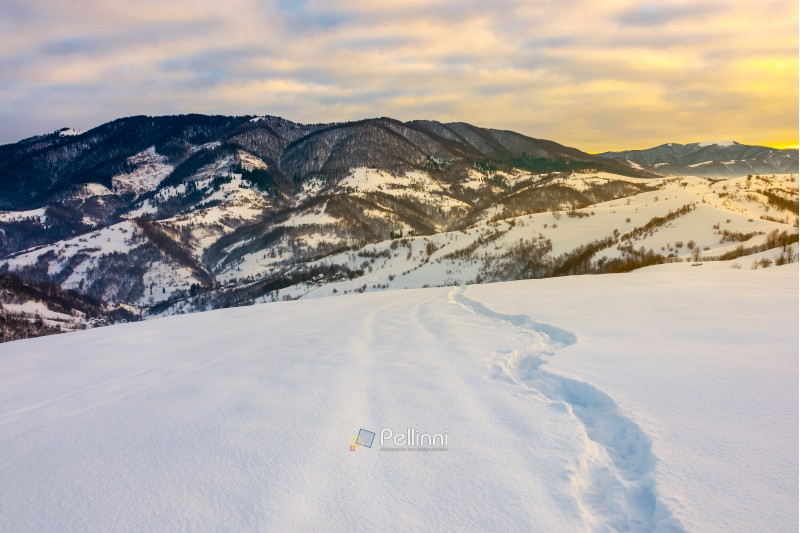 winding foot path through snowy slope in mountains. gorgeous winter landscape at sunrise with cloudy sky