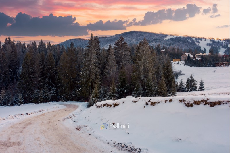 wonderful winter countryside in mountains at dusk. road winds down the slope in to the forest. village on a snowy hill in the distance. beautiful evening sky with clouds