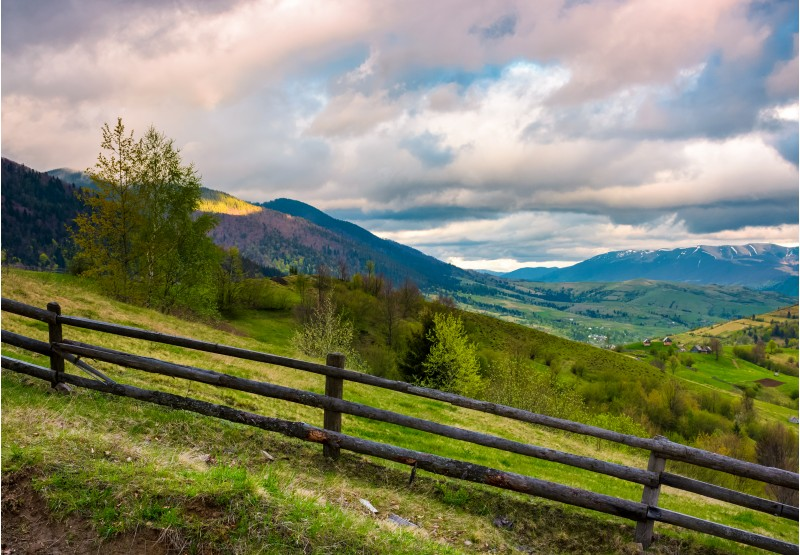 wooden fence across the hill. beautiful agriculture scenery of Carpathian mountains on a cloudy springtime day