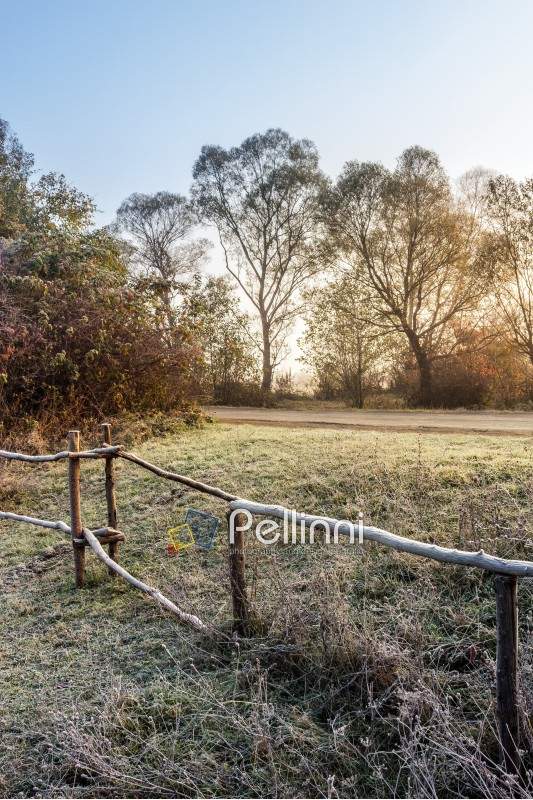 wooden fence in foggy morning among the frozen grass on hillside near the village