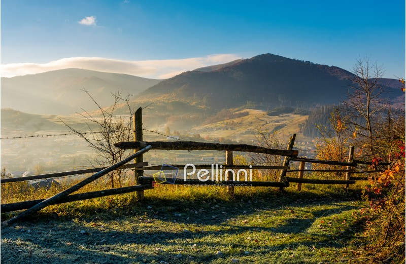 wooden fence near forest on hillside above the village valley. lovely autumnal countryside nature background in mountains at sunrise