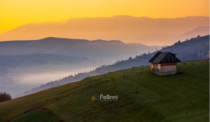 woodshed on a hillside at sunrise. beautiful countryside scenery of mountainous area. yellow sky over the purple mountains. fog down the valley of Synevir village, TransCarpathia, Ukraine