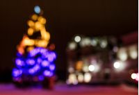 Abstract Christmas lights background at night. Christmas tree on the city square blurred with bokeh effect