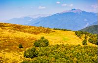 Polonyna Krasna Range of Carpathian Mountains with its peaks, hills, meadows and forests under the blue sky with clouds in late summer day