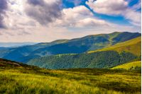 Carpathian Mountains with its peaks, hills and grassy meadows under the blue sky with clouds in summer day