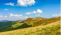 Polonyna Krasna landscape. Ridge of Carpathian Mountains with its peaks, hills, meadows and forests. Blue sky with clouds in late summer day