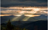 Carpathian valley lit by sunbeams. Spectacular mountain landscape at cloudy sunset