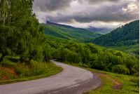 Empty asphalt countryside road winding in mountains. Beautiful Carpathian landscape at cloudy sunrise