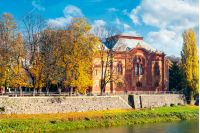 Uzhgorod, Ukraine - NOV 10, 2012: Philharmonic Orchestra Concert Hall on the bank of the river Uzh in autumn. former building of synagogue is a popular tourist attraction. beautiful sunny weather with yellow foliage