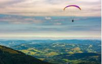 Skydiver flying in the clouds over the rural valley at sunset. parachute extreme sport
