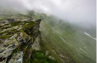edge of steep slope on rocky hillside in foggy weather. dramatic scenery in mountains