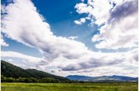 agricultural fields in mountainous countryside. lovely landscape with gorgeous cloudy sky