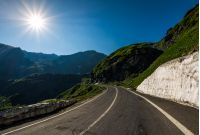 asphalt road uphill through mountain range. snow and grass on hillside under the clear blue sky with sun