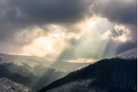 beams of light over the mountains. gorgeous scenery on a cloudy day in winter