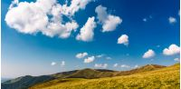 beautiful cloud formations on a deep blue sky. lovely panoramic landscape of mountain ridge