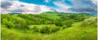 beautiful countryside panorama in springtime. grassy hills and meadows. trees with green foliage on hillsides. mountain top in the distance. wonderful nature scenery of Carpathians