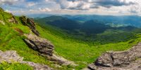 beautiful panorama of mountainous landscape. view from the edge of a hillside with cliffs. Borzhava ridge and Runa mountain in the distance. village down in the valley. lovely summer scenery
