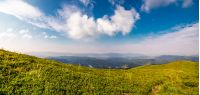 beautiful panorama of mountainous landscape. blue sky with some clouds over the grassy slope of a mountain ridge. lovely summer weather