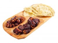 beer snack on the wooden plate. grilled pork ribs and chicken wings with italian pita bread chips