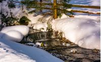 brook with cascades in winter forest. lovely winter nature scenery