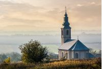 church on a hill over the hazy rural valley at sunset. lovely autumn countryside scenery
