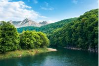 composite landscape with river in mountains. trees and cliff on the riverbank. high tatra ridge in the distance. wonderful sunny weather with blue sky. beautiful summer scenery