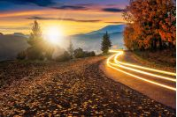 road; car lights; landscape; morning; mountain; nature; sky; autumn; tree; travel; view; environment; hill; season; cloud; beautiful; idyllic; dusk; ridge; valley; weather; dramatic; village; countryside; winding; foliage; asphalt; curve; way; destination; speed; ride; mount; fall; road; serpentine; wide; high; peak; tourism; sun; sunset; light; sunlight; ray; beam; flare; dawn; evening; scenic