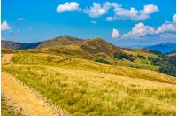 dirt road through alpine hills of mountain ridge. beautiful early autumn landscape in fine weather under blue sky with clouds