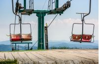 empty ski elevator with red chairs on top of a hill Gymba. Carpathian mountain ridge Borzhava, Ukraine. Lovely mountain landscape with clear sky