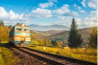 fast moving train in autumn mountains. wonderful autumn countryside at sunrise. village down in the valley. beautiful sky over the distant ridge