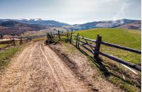 fence along the country road in rural area. lovely agricultural landscape in Carpathian mountains. grassy fields on hill in springtime. Location Volovets, Ukraine