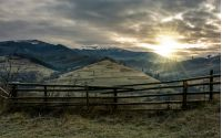 fence on hillside in late autumn gloomy sunrise. high mountain ridge with snowy tops in a distance under overcast sky