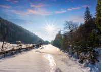frozen river in forested mountains. beautiful scenery with spruce trees and village on the banks