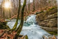 frozen waterfall over the huge boulder on the river among empty forest with old brown foliage on the ground