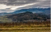 gloomy morning in mountains. autumnal scenery with snowy mountain tops