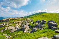 grassy slope with huge rocks. wonderful summer landscape in mountains. grassy meadow with huge boulders. beautiful sunny landscape. mountains in summertime