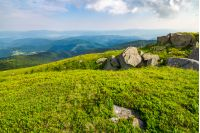 grassy slope with huge rocks. wonderful summer landscape in mountains. grassy slope with huge rocks. wonderful summer landscape in mountains