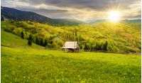 hay shed on a grassy field in mountains. beautiful countryside landscape in springtime at sunset in evening light. cloudy afternoon. village on the distant hills
