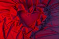 love card. heart made of a red fabric in blue light