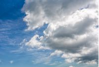 heavy grey cloud on a blue summer sky. dramatic weather background with dynamic cloud arrangement