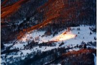 hillside in red light on winter sunrise. beautiful nature scenery in mountains