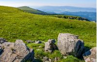 mountain summer landscape. meadow with huge rocks among the grass on top of the hillside near the peak of mountain ridge