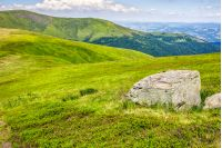 mountain summer landscape. meadow with huge stone among the grass on top