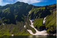 clear lake in mountains with snow and grass on rocky hillside. fine weather in picturesque summer scenery