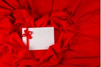 love card. white card with a red ribbon on a red fabric